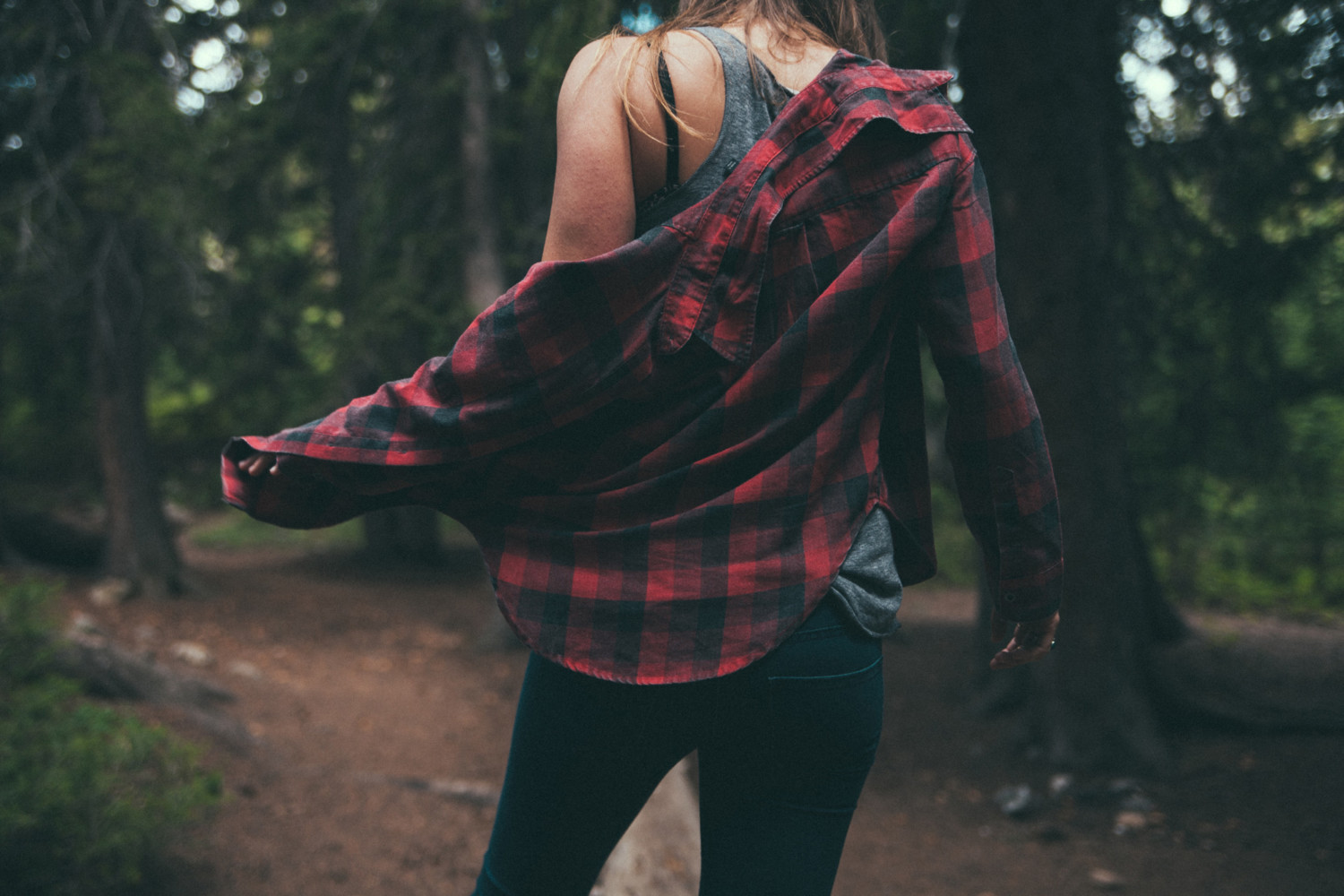 A girl with plaid shirt in jungle.