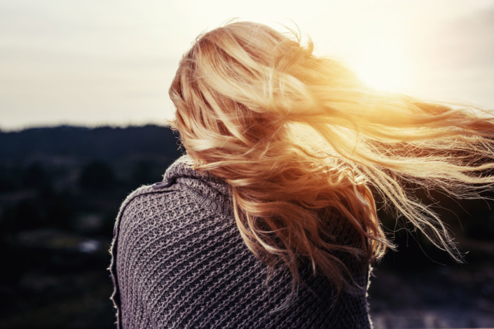 Blonde girl in front of the sun.